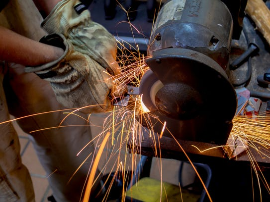 Nathan Williams working on bench grinder at their shop,