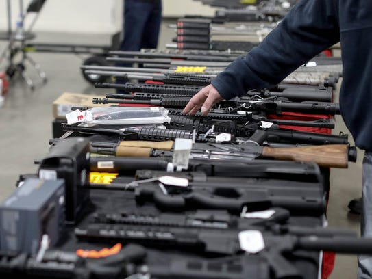 Semi-automatic weapons and rifles are on a table for