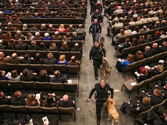 Law enforcement officers walk K-9 officers past the