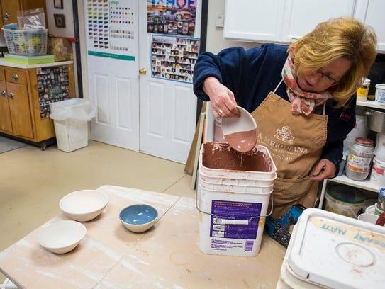 Deborah Bassett-Maxwell dips a bowl into glaze in her