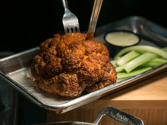 Buffalo cauliflower is cauliflower bites tossed in buffalo sauce and served with celery sticks and blue cheese dipping sauce.