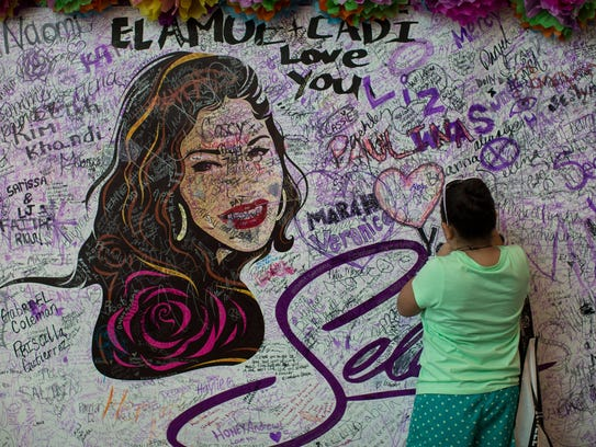 A young girl signs her name on the Selena mural in