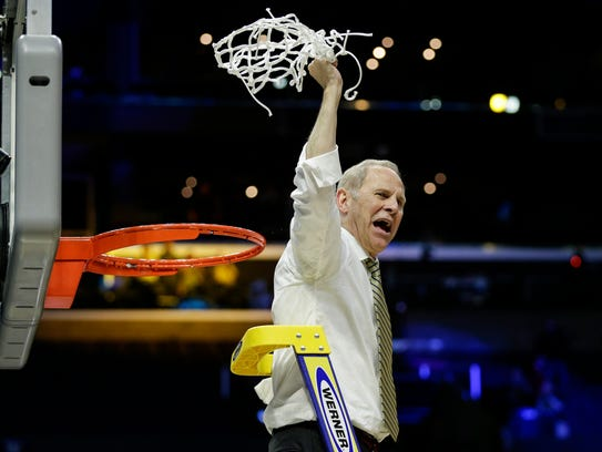 John Beilein celebrates the cutting of the net after Michigan defeated Florida State.