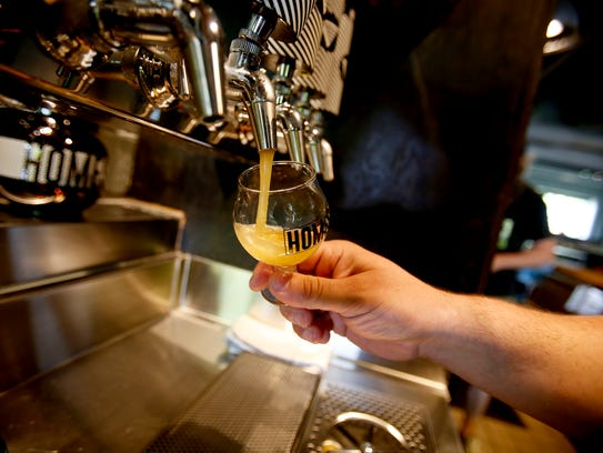 Beer being poured for a customer at HOMES Brewery on