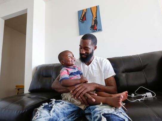 Isaiah Phlegm plays with his son Isaiah Jr., 1, in their apartment in Southfield, on June 6, 2018.