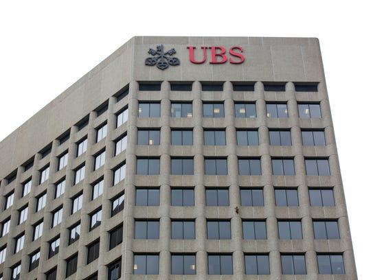 A raccoon scales the side of the UBS Tower in downtown