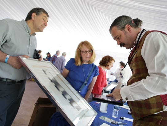 """Nicholas Lowry of New York City, right, appraises an artwork during the visit by """"Antiques Roadshow"""" at Meadow Brook Hall in Rochester Hills."""