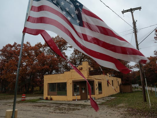 A tattered american flag flaps in the wind in front