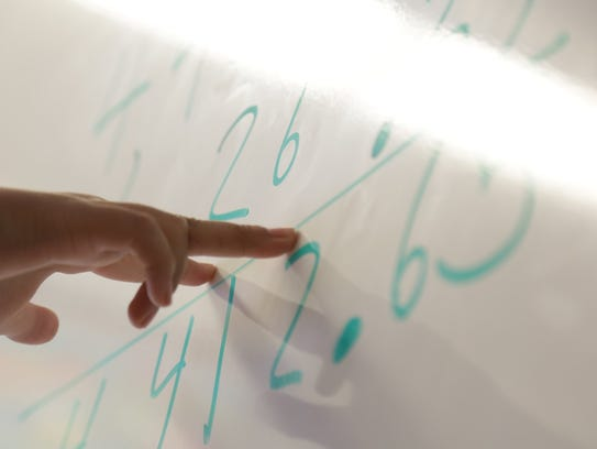 A student solves a math problem during class on May