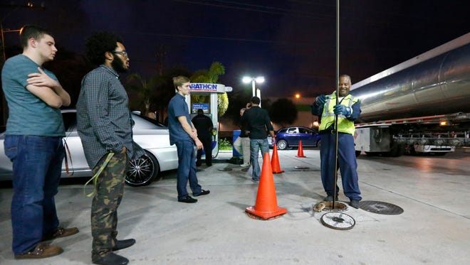 Motorists look on as Wayne Demps with CWC Transportation, right, measures the amount of gasoline he pumped into the tanks of a Marathon gasoline station, Wednesday, Oct. 5, 2016, in Hollywood, Fla.