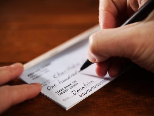 Close up View of Hand Writing A Donation Check