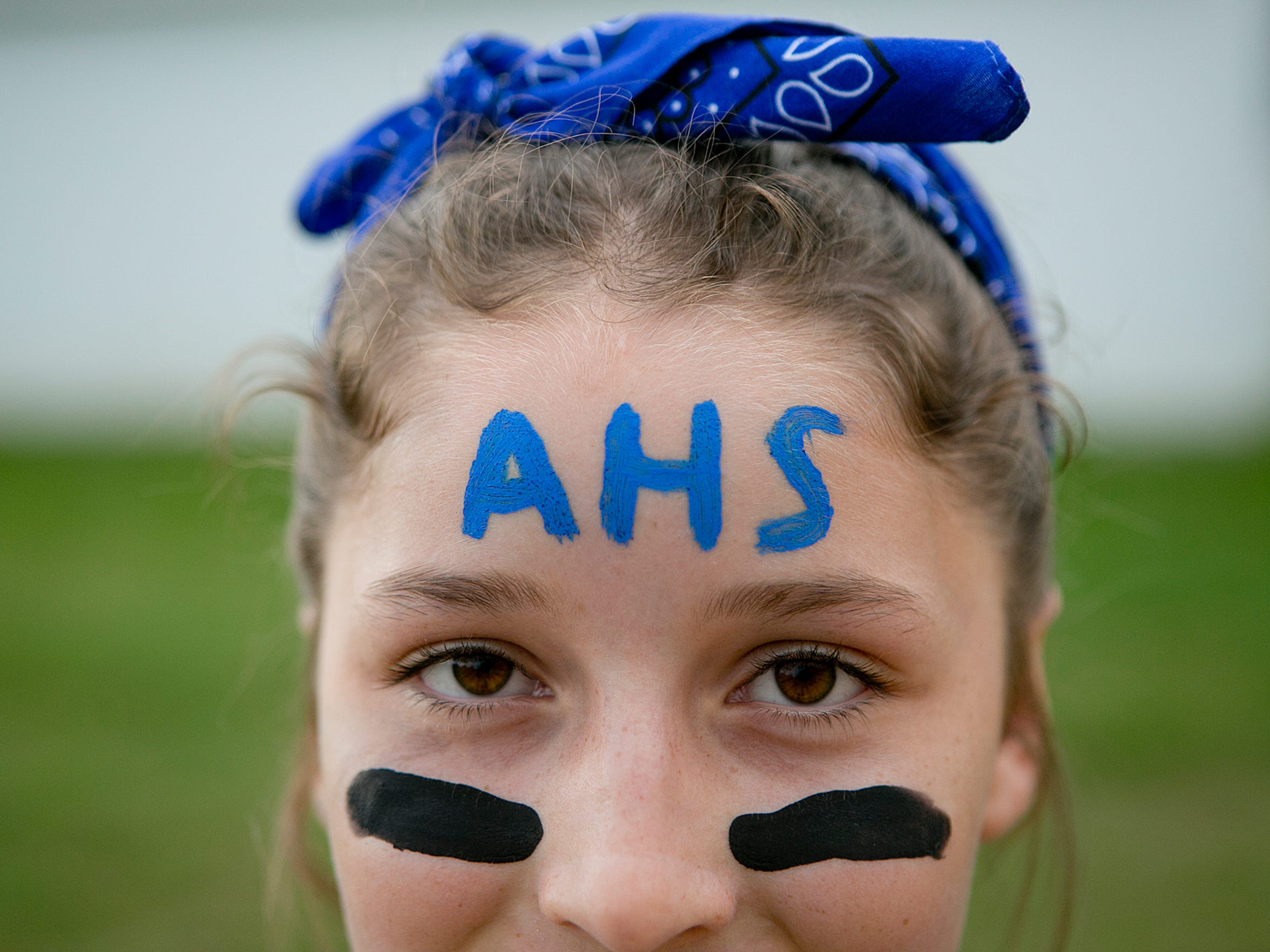 Stephanie Bandy, 11, shows off her Amherst pride with face paint before the non-conference football game against Omro at Amherst High School, Friday, Aug. 21, 2015.