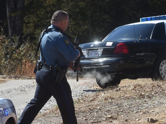 An Arkansas State Trooper carries a semi-automatic