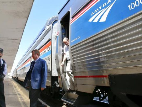 An Amtrak conductor looks down the track as the train