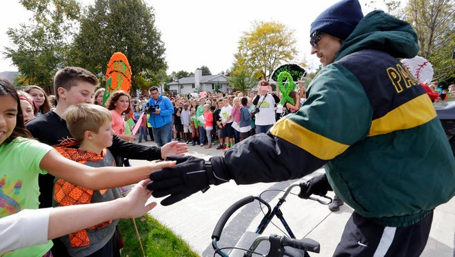 Teacher Jeff Petrie greets students from Riverview Middle School Friday October 7, 2016 in Plymouth following a special parade in honor of him for homecoming. Students held signs of support and shouted encouraging chants.