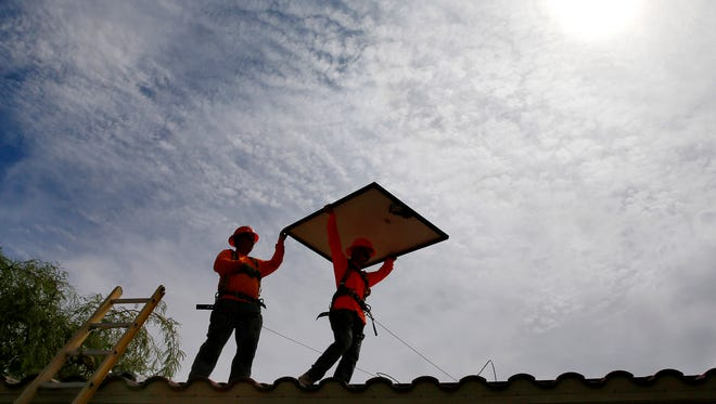 In this July 28, 2015 file photo, electricians install solar panels on a roof for Arizona Public Service company in Goodyear, Ariz. Corporation Commissioner Andy Tobin wants to see 80 percent of Arizona's energy come from 'clean' resources by 2050.
