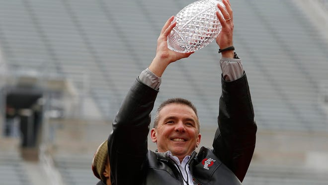 Buckeyes head coach Urban Meyer with the Coaches Trophy during the national championship celebration at Ohio Stadium in January.