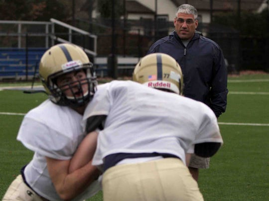 Rye Country Day School football coach John Calandros oversees blocking drills during practice on the school field Nov. 15, 2011.