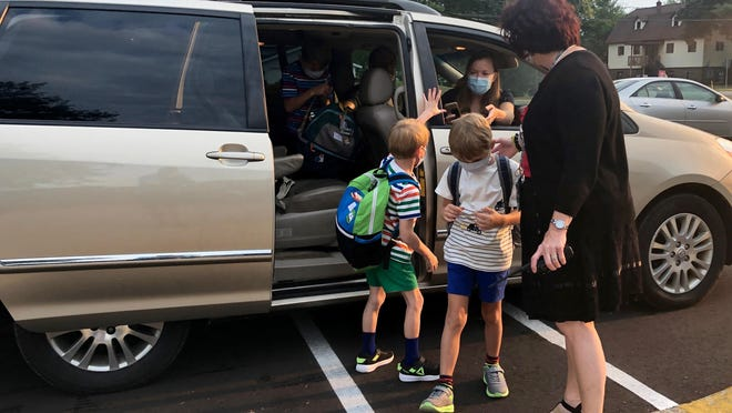 Holland West Elementary principal Kathleen Ramirez greets students on the first day of school Wednesday, Aug. 26.