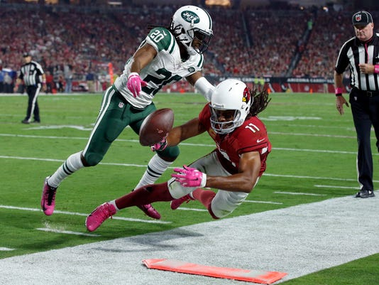 Arizona Cardinals wide receiver Larry Fitzgerald (11) is knocked out of bounds after the catch by New York Jets cornerback Marcus Williams (20) during the first half of an NFL football game, Monday, Oct. 17, 2016, in Glendale, Ariz. (AP Photo/Ross D. Franklin)