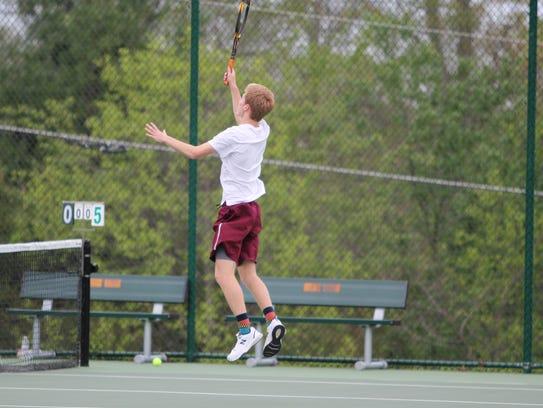 Senior Micah Davis leaves his feet to return a volley