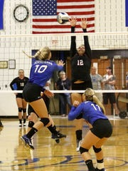 Elmira's Mariah Gonzalez goes up for a block of a spike by Horseheads' Makenzie Osgood during the Blue Raiders' 3-1 win Tuesday at Horseheads Middle School.