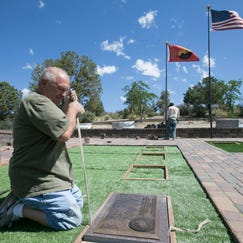 Ken Cadwallader places a memorial marker for fallen Granite Mountain Hotshot Travis Carter at the Arizona Pioneers' Home Cemetery.