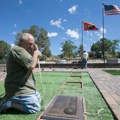 Ken Cadwallader places a memorial marker for fallen Granite Mountain Hotshot Travis Carter at the Arizona Pioneers' Home Cemetery.