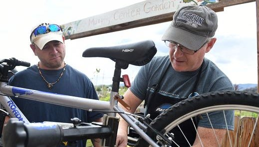 Mark Brewer, right and Ricky Glaum work on Ricky's bike at the Murphy Center on Friday, September 30, 2016. Volunteers help the homeless overcome transportation issues each Friday, by repairing bikes and trailers.