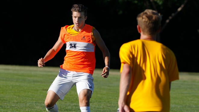 Marquette high school senior  Sam Holton practices with teammates at Quad Field.