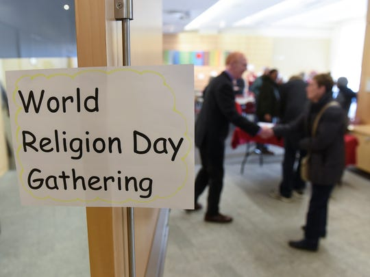 People are greeted before the start of a celebration of world religions organized by the Baha'is of Central Minnesota Saturday, Jan. 14, 2017, at the St. Cloud Public Library.