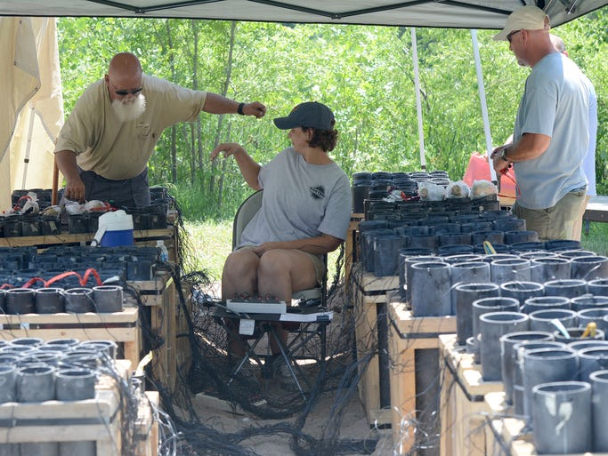Charlie Dravis, left, a park technician with the City of Fort Collins Parks Department, Marsha Evanoff, middle, of Western Enterprises, based in Carrier Oklahoma, and Matthew Evanoff, right, of Western Enterprises, load and wire charges as they prepare the 4th of July fireworks on a small peninsula on the west side of Sheldon Lake in City Park.  Thursday July 3, 2014. The process takes a little more than two days to set up.