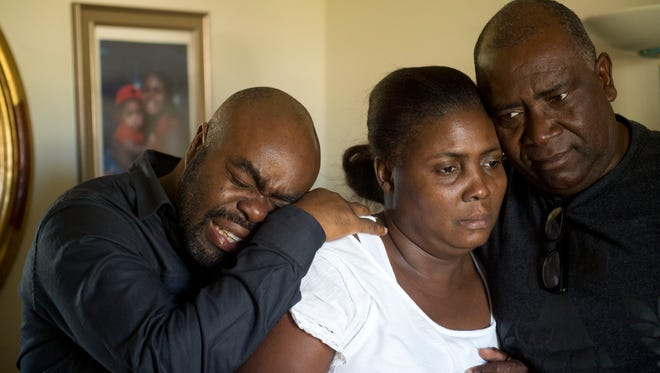 """Venel Vaillant, Sr. (left) and Magie Vaillant (center), the parents of 16-year-old Venel Vaillant, who died Saturday after drowning in Jensen Beach after struggling with a rip current in the ocean, are comforted by family friend Favin Leger, of Fort Pierce, on Monday at their home in Port St. Lucie. """"We are family,"""" Leger said."""