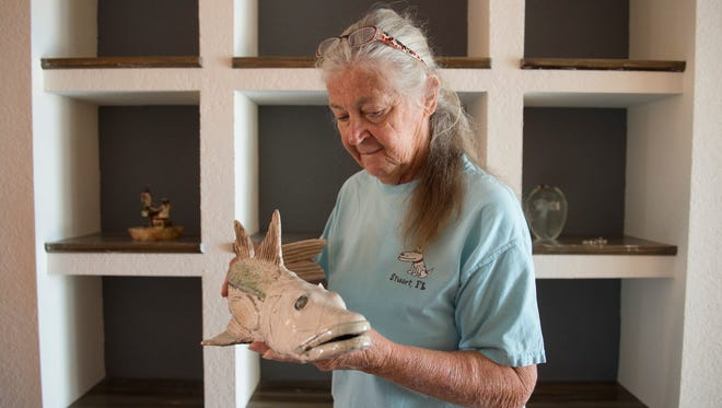 "Marcia Foosaner, 70, packs up her belongings, including a snook fish made from raku pottery and given to her by a friend, on May 29 at her Palm City home. Foosaner is in the process of moving to Lake Placid after making a tough decision last winter to leave Martin County, where she spent nearly 30 years as a fishing guide. She retired after she felt the St. Lucie River and Indian River Lagoon were too polluted to fish on. ""I'm moving because this to me is no longer a happy place to be. It's not the happy place that I've been going to for the last 29 1/2 years,"" Foosaner said."