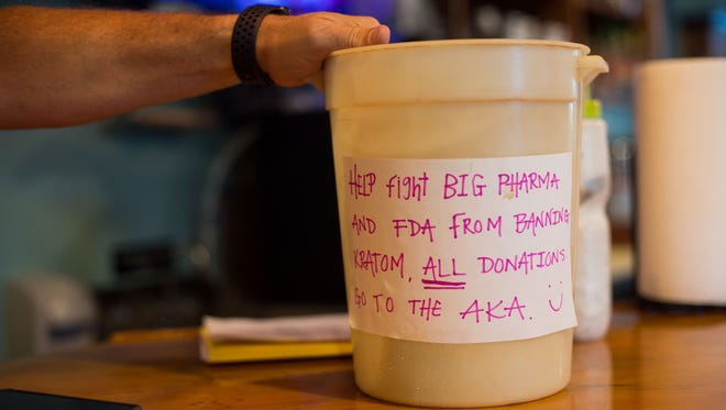 """The Island Root Kava Bar in Stuart has a bucket at the bar labeled for donations to go to the American Kratom Association, seen June 13, 2018, in downtown Stuart. According to their website, the AKA, which advocates for the botanical substance, """"...was formed in 2014 and officially launched in 2015, to protect the right of all Americans to use the natural botanical Kratom for improved health and well-being."""""""