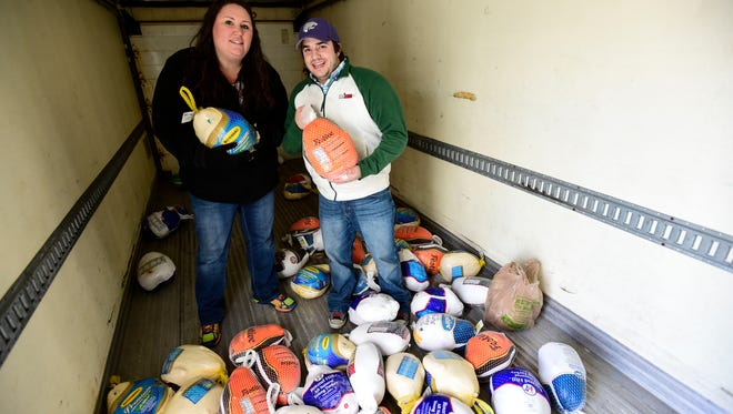 Endicott residents Lori Martin, left, Mix Morning Show host, and Matt Gapske, right, program director for 105.7, stand in a truck holding turkeys at the 2014 holiday collection organized by Catholic Charities of Broome County.
