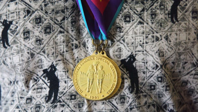 Ingold Hahn of Waynesboro, a lifelong swimmer, shows off one of two gold medals he won for the butterfly and back strokes in Special Olympics international competitions.