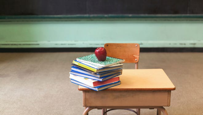 Stack of school books and apple on desk in empty classroom.