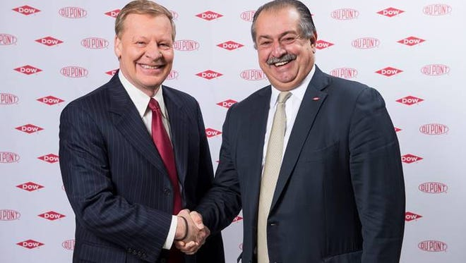 DuPont Chief Executive Ed Breen (left) shakes the hand of Dow Chemical Chief Executive Andrew Liveras to celebrate a merger between the two companies.