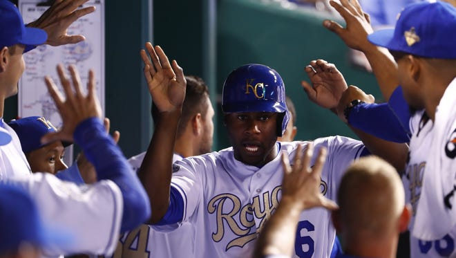 Lorenzo Cain #6 of the Kansas City Royals is congratulated by teammates in the dugout.