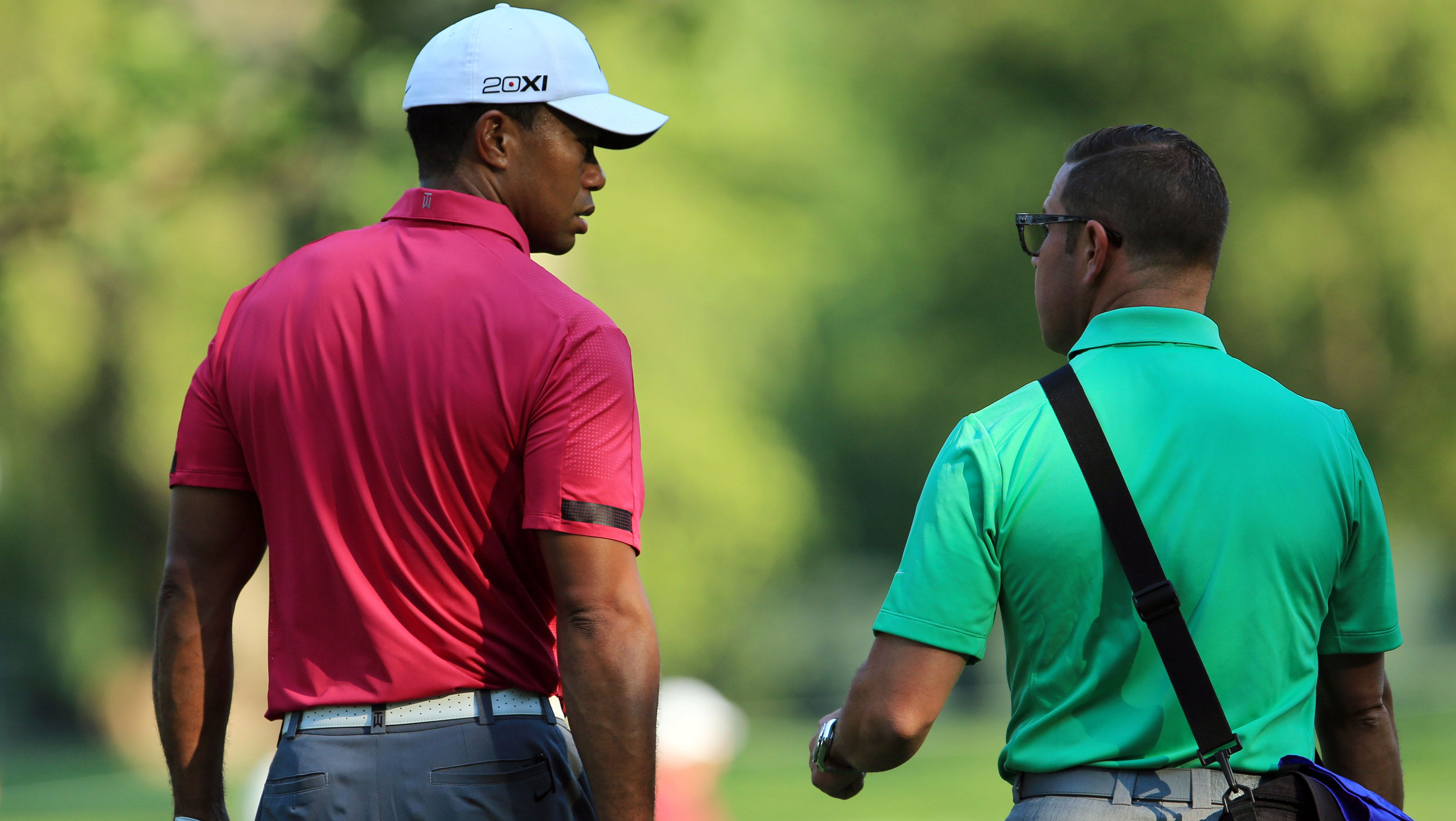 Tiger Woods talks with his coach Sean Foley during the practice round of the 95th PGA Championship at Oak Hill Country Club. The coach winning the pastel color war between the two.