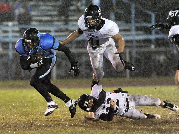 Bishop Kearney's Tre Johnson, left, eludes the pursuit of LeRoy's Steve Cappotelli, top, and Tom Kelso during a game played at Bishop Kearney High School on Sept 13, 2013.