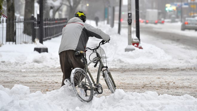 A cyclist lifts his bike over a snow bank on Pearl Street in Burlington on Tuesday.