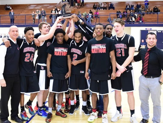 Churchill basketball team members hold up the school's