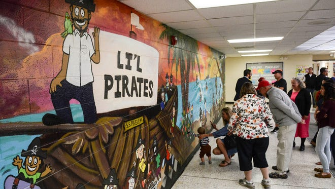 Parents and students at Palm Bay Elem. examine a new mural created by the school's Community Problem Solving team along with artist Christopher Maslow.