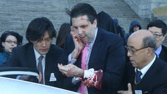 Mark Lippert covers a wound to his face as he leaves
