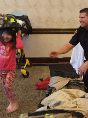 Cadence Phou tries on a firefighting helmet during Canton's Community Connection Day on Saturday as Karl Brichford, a firefighter/paramedic, looks on.