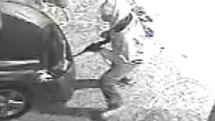 Surveillance caught this image of the gunman in a trio of home invaders by the car of a woman they confronted as she got home from work in January.