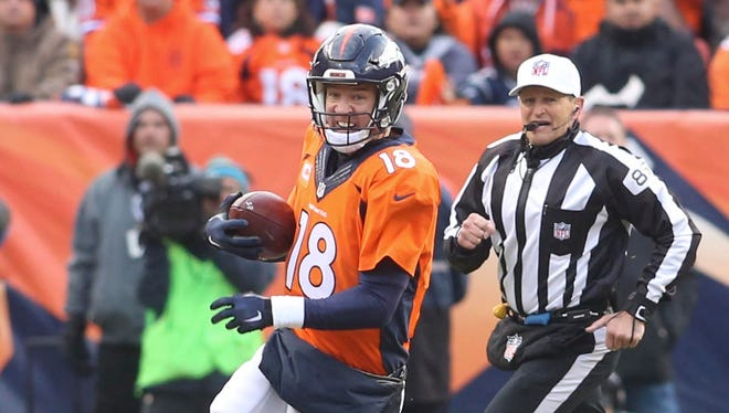 Denver Broncos quarterback Peyton Manning (18) scrambles for yards during the  second half in the AFC Championship football game at Sports Authority Field at Mile High.