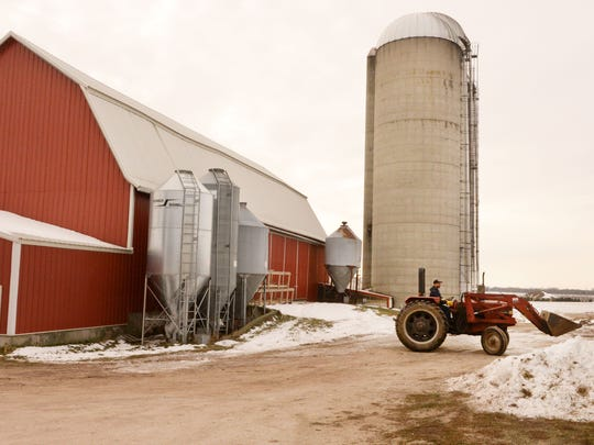 Steve Leitner drives a tractor through the farm yard at the Marsh Edge Dairy near the Collins Marsh.